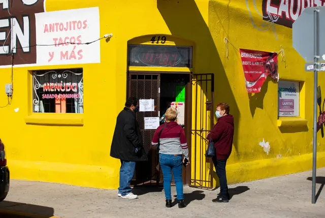 People wait outside an El Paso restaurant to pick up their food orders after the county judge ordered a shutdown of nonessential businesses. A state appeals court has halted the shutdown. Credit: Ivan Pierre Aguirre for The Texas Tribune
