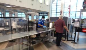 A TSA officer at ELP airport conducts airport security checkpoint screening of passenger's carry-on bags, using CT technology. | Photo courtesy TSA