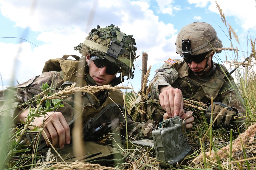U.S. Army Staff Sgt. Robert Moore (right), with 1st Squadron, 2nd Cavalry Regiment, helps U.K. Army LT. Tom Chapman (left), assigned to the 1st The Queen's Dragoon Guards, set up M18A1 Claymore mine during a multinational claymore training exercise with Battle Group Poland at Bemowo Piskie Training Area, Poland on July 10, 2018. Battle Group Poland is a unique, multinational coalition of U.S., U.K., Croatian and Romanian Soldiers who serve with the Polish 15th Mechanized Brigade as a deterrence force in support of NATO's Enhanced Forward Presence. |  U.S. Army photo by Spc. Hubert D. Delany III /22nd Mobile Public Affairs