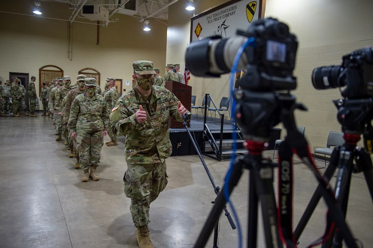 "A Soldier with the 345th Combat Sustainment Support Battalion gives a ""thumbs up"" gesture to cameras broadcasting a virtual send-off ceremony at the National Guard armory in Ada, Oklahoma, April 1, 2021. The Soldiers are being mobilized to Fort Bliss, Texas in order to provide COVID mitigation support to units deploying overseas.   