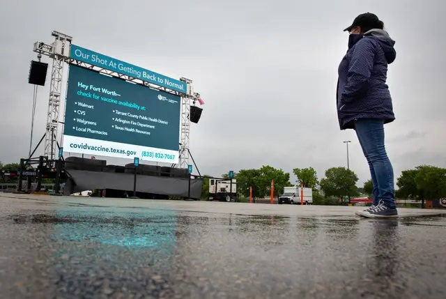 Susan Valadez looks at a Texas Department of State Health Services advertisement encouraging people to get the COVID-19 vaccine before she enters a Walmart in Fort Worth on April 30, 2021. Credit: Shelby Tauber for The Texas Tribune