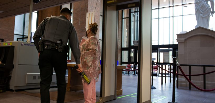 A security guard performs a check on a visitor to the El Paso County Courthouse on Monday. Many county offices are still not open to visitors.  |  Corrie Boudreaux/El Paso Matters
