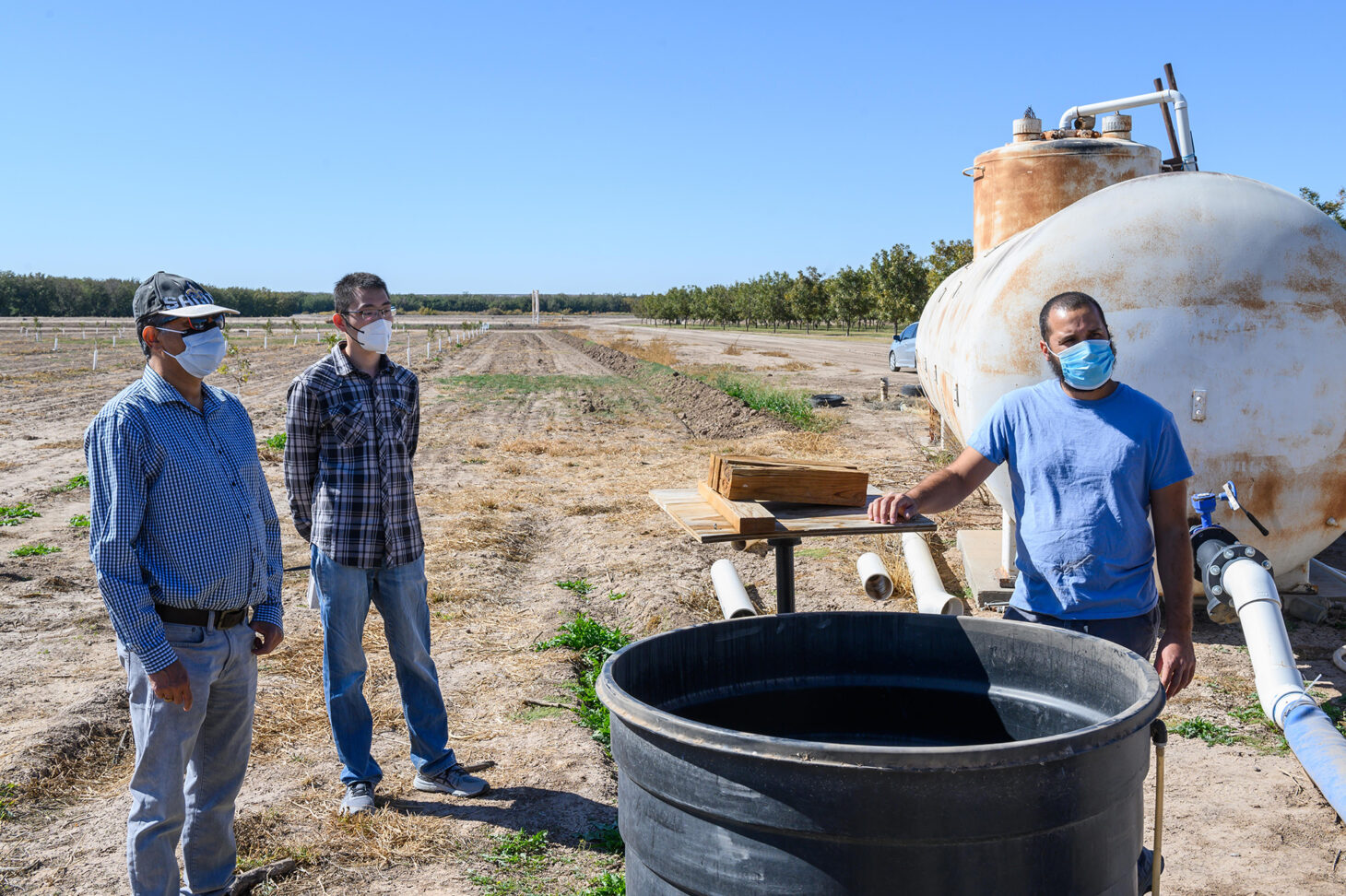 New Mexico State University College of Agricultural, Consumer and Environmental Sciences professor Manoj Shukla, left, Chang Liu, center and Adam Gonzalez, right, explain the N-Drip's Gravity Micro Irrigation system at NMSU's Leyendecker Plant Science Research Center  | Photo courtesy NMSU