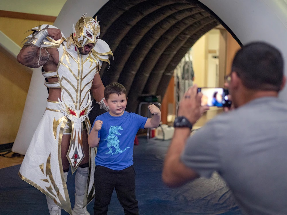 """Army kid Jonah Orozco grabs a photo with a luchadore with help from dad, Sgt. Jaime Orozco, at the FMWR Lucha Libre wrestling event at Fort Bliss, Texas, July 23, 2021. """"The best part was 'the Dragon' versus the chosen one,"""" said Jonah, """"I had fun.""""  
