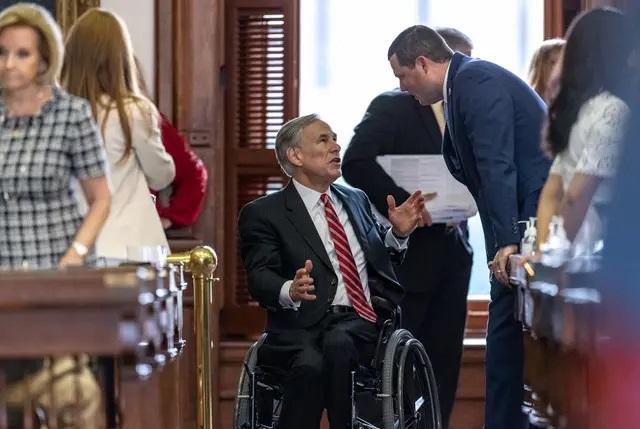 Gov. Greg Abbott speaks with lawmakers on the House floor. Credit: Jordan Vonderhaar for The Texas Tribune