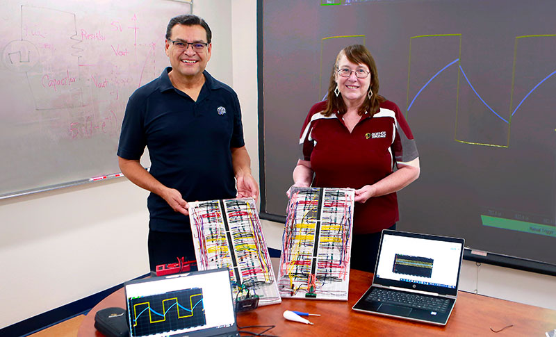 """UTEP's David Zubia, Ph.D., professor of electrical and computer engineering, and Lisa Roth, a science teacher at Gadsden High School, were part of a summer partnership organized by Project ACE, a program created to increase the number of underrepresented students who pursue undergraduate degrees in engineering as well as biomedical and behavioral sciences. Roth built and tested a """"Personal Lab"""" circuit board that Zubia created and patented. Photo: Laura Trejo / UTEP Communications"""
