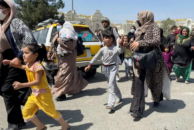 Women and children try to get inside Hamid Karzai International Airport in Kabul, Afghanistan. Credit: REUTERS