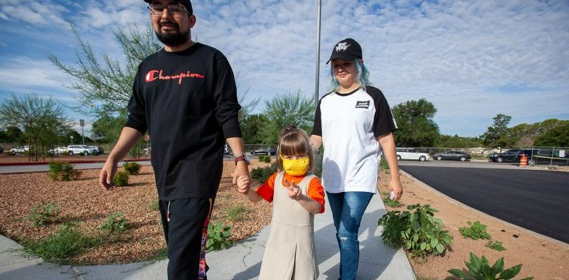 A family walks toward Don Haskins PK-8 School as El Paso Independent School District opens the new facility on Aug. 2.  |  Corrie Boudreaux/El Paso Matters