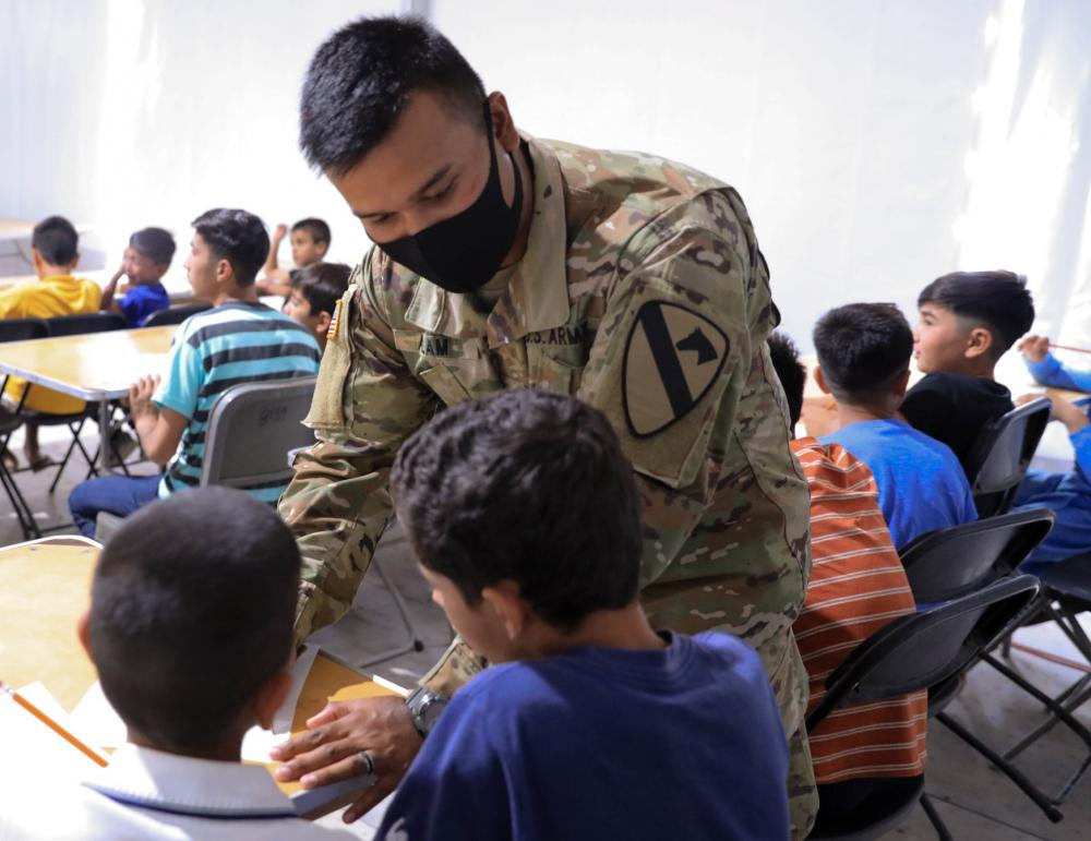 Spc. Jahadul Alam, a UH-60 Black Hawk helicopter repairer with 2nd Battalion, 227th Aviation Regiment, 1st Cavalry Division out of Fort Hood, Texas, helps a young Afghan evacuee write words in English during the language and education class at Fort Bliss' Doña Ana Complex in New Mexico, Sept. 24, 2021  | Photo by Sgt. Christina Westover, 24th Theater Public Affairs Support Element