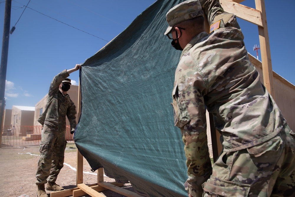 U.S. Army Sgt. Taylor Douglas and Spc. Derrick Reutebuch, assigned to the 40th Brigade Engineer Battalion, 2nd Armored Brigade Combat Team, 1st Armored Division, hang a divider for a privacy partition Aug. 29, 2021, at Fort Bliss' Doña Ana Complex in New Mexico. |   U.S. Army photo by Sgt. Quintin Gee