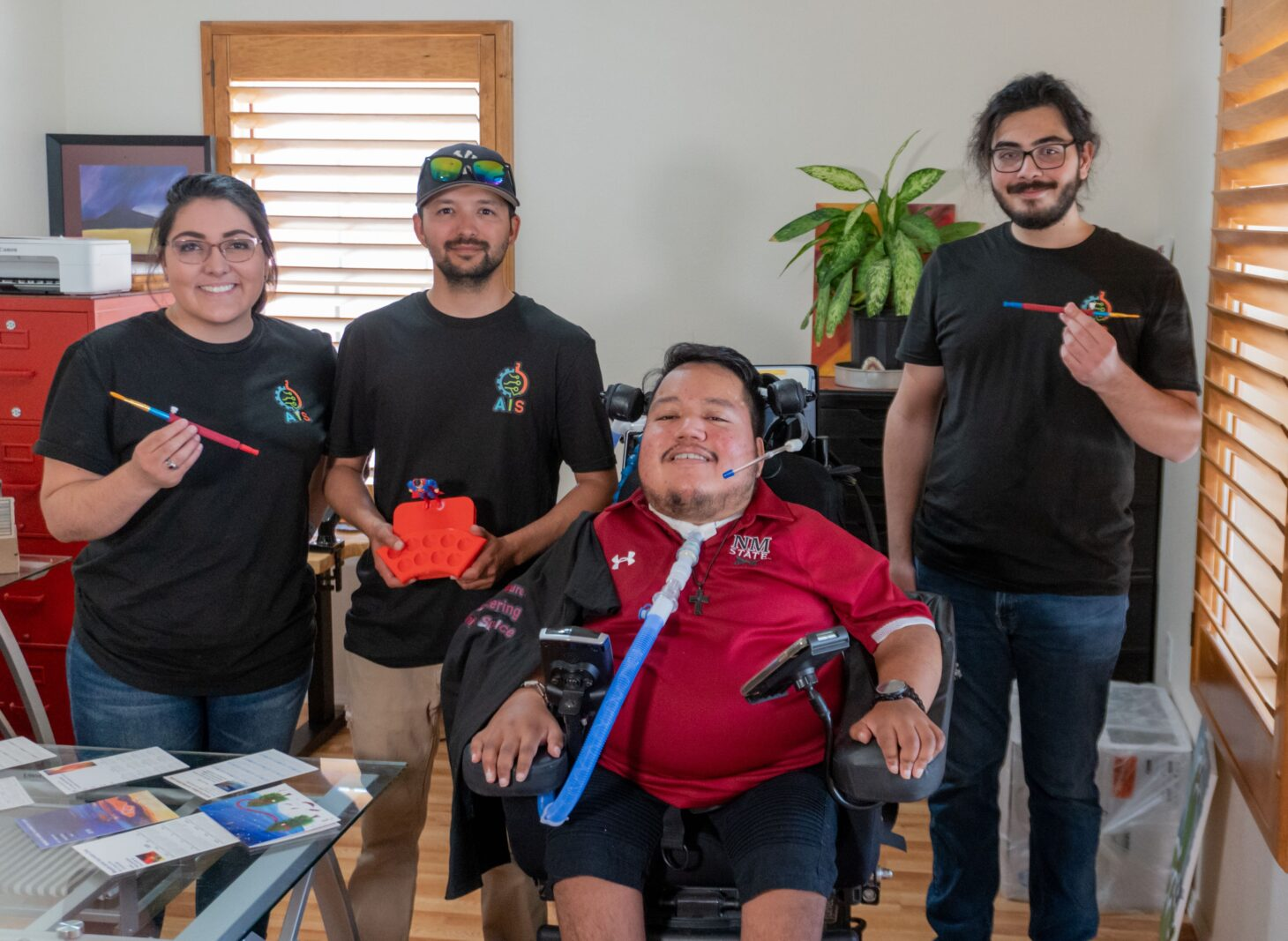 NMSU engineering students (left to right) Amanda Stoyanoff, Joshua Santana and Sami Naser with Sam Cueto (seated), show off the new art station that was created specifically for Cueto as part of their graduation requirements.  | NMSU photo by Vladimir Avina