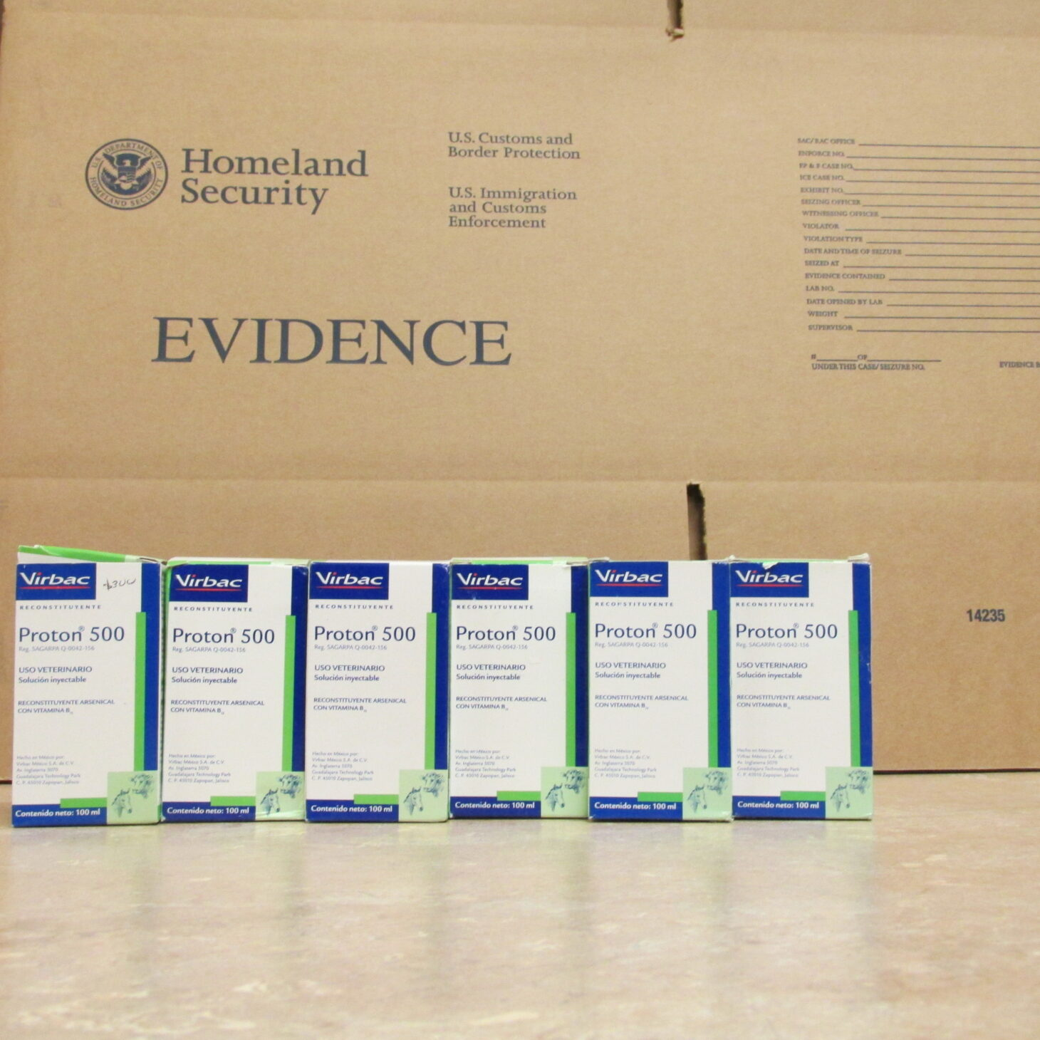 6 boxes of horse drugs on a table, with a Homeland Security Logo behind